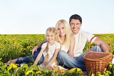 A happy family with a child at a picnic in a field photo