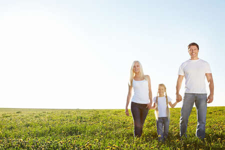family grass: Young happy family in a field