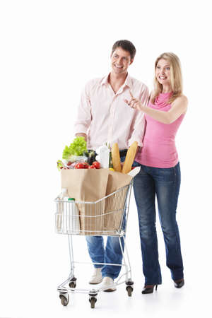 woman shopping cart: The happy couple with a cart with food on a white background
