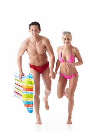 activity holiday: Running a young couple in bathing suits isolated