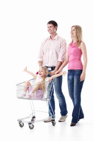 ni�os de compras: Pareja joven con un ni�o con un carrito de compras aisladas Foto de archivo