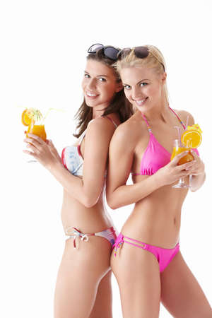 Two young attractive girl with a cocktail on a white background photo