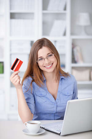 Young girl with laptop and credit card at home photo