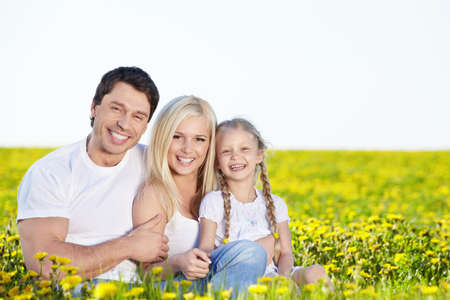 family grass: Happy young family in the field Stock Photo