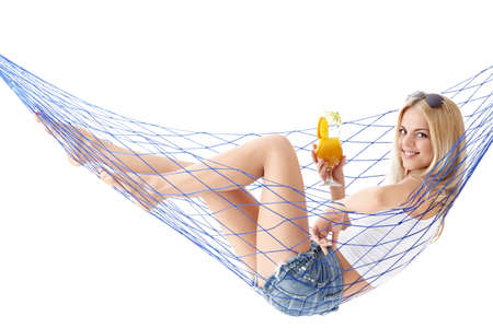 Attractive girl with a cocktail in a hammock isolated photo