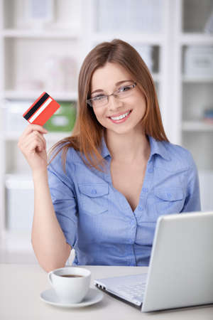 credit cards: A beautiful girl with a laptop and a credit card at home