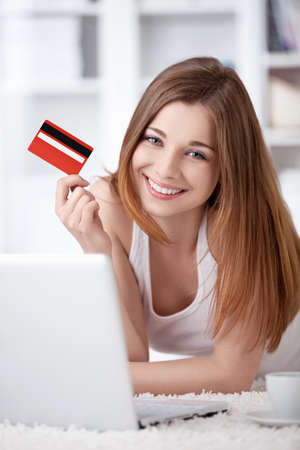 A young girl with a laptop and a credit card at home photo