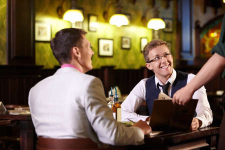 The waiter shows men in a pub menu photo