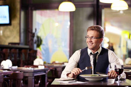 A young man having dinner in a restaurant Stock Photo - 9997015