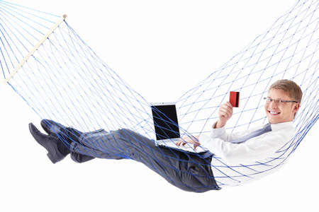 A young man with laptop and credit card in a hammock Stock Photo - 9997023