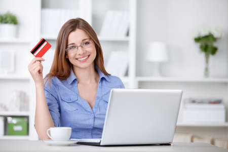 An attractive young girl with laptop and credit card photo