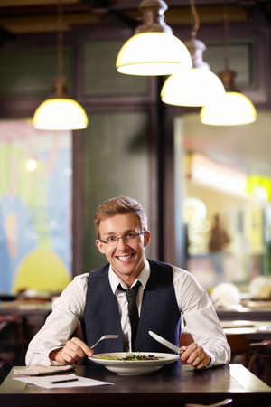Young smiling man in a restaurant photo
