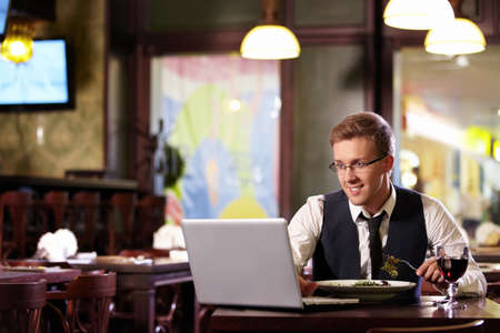 A young man with a laptop in a restaurant photo