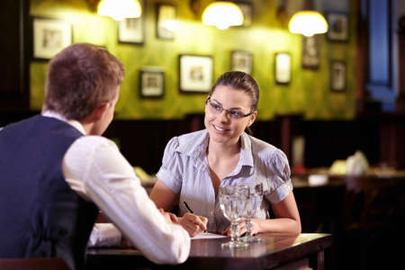 interviewing: A young girl writes in a restaurant