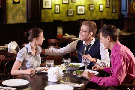 Young people communicate during a dinner at a restaurant photo