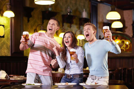 sports bar: Young people with a beer in a restaurant Stock Photo