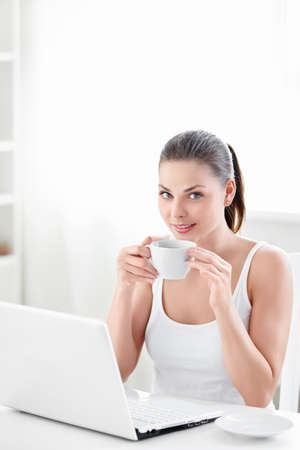 A beautiful girl with a cup and a laptop photo
