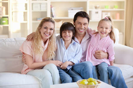 family on couch: Happy family with children at home Stock Photo