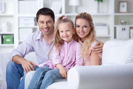 familia abrazo: Una familia feliz con un ni�o en el hogar Foto de archivo