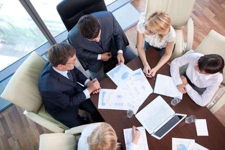 Mensen uit het bedrijfsleven aan de onderhandelingstafel in het kantoor Stockfoto