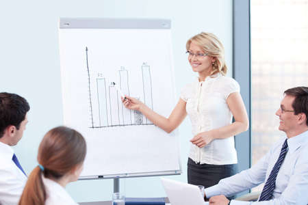 tells: An attractive woman tells a presentation at the office