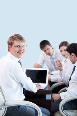 Young businessman with laptop on the background of employees in the office photo
