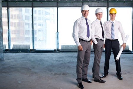 construction safety: Young men in shirts and helmets on a construction site Stock Photo