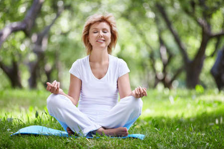 mature women only: Mature woman in a park yoga