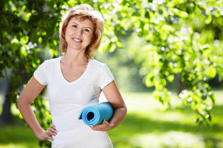 Mujer madura en un parque con un tapete de Gimnasia Foto de archivo - 10259559