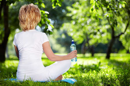 A woman in a park in the lotus position photo