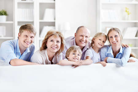 a generation: Happy family with children and grandchildren on the couch