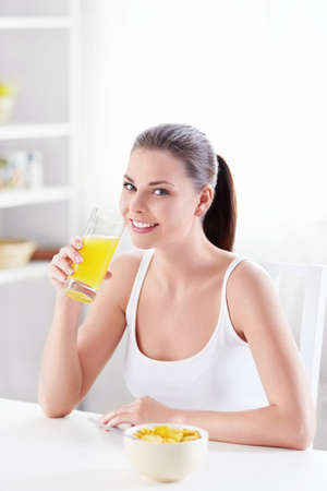 jus orange glazen: Jong meisje aten ontbijt in de keuken