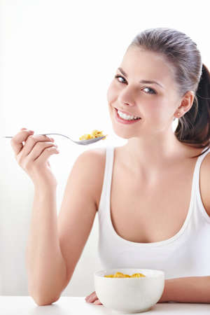 cornflakes: Young attractive girl at breakfast Stock Photo