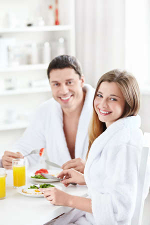 eating breakfast: Young happy couple at breakfast in the kitchen Stock Photo