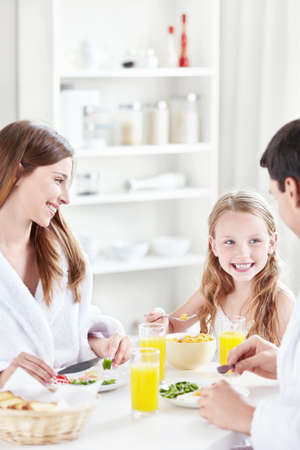 A happy family with a child eat breakfast in the kitchen photo