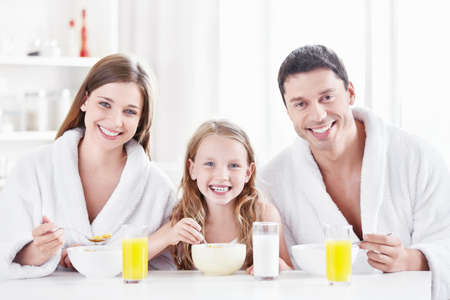 children breakfast: A happy family with a child in the morning in the kitchen