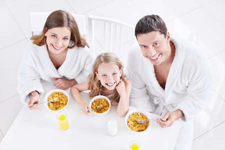 A happy family with a child eating breakfast photo