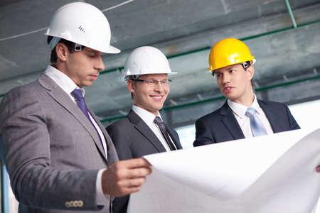 planos arquitecto: Hombres de traje en una obra