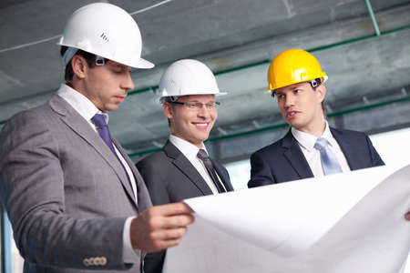 architect plans: Men in suits at a construction site