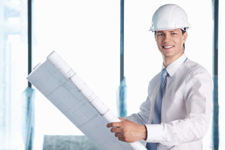 young engineer: A man in a helmet with a plan for construction