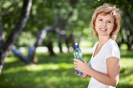 mature women only: Mature woman with a bottle of water in the park Stock Photo