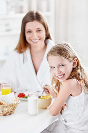 Mother and daughter eating breakfast in the kitchen photo