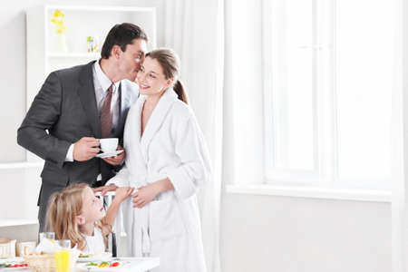 going out: The husband kisses his wife before going out in the kitchen Stock Photo