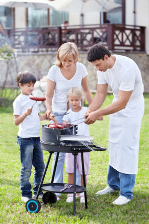 Happy family cooks sausages outdoors photo
