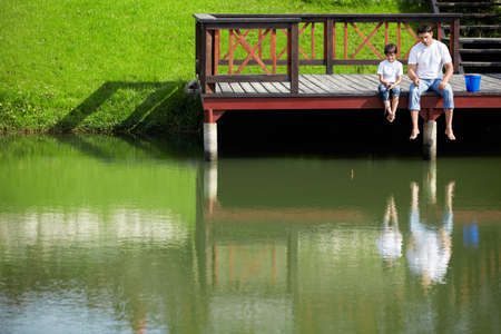 children pond: Father and son fishing Stock Photo