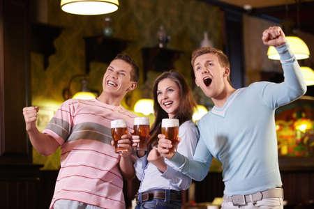 hombre tomando cerveza: Fans de la cerveza en un pub Foto de archivo