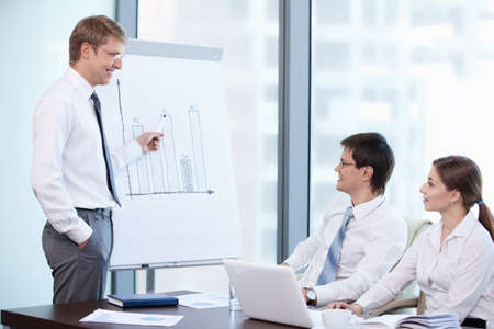 A young man shows a graph of the office Stock Photo - 10498156