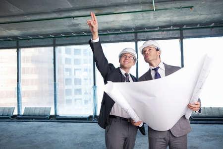 supervisores: Dos hombres en cascos en sitio de construcci�n