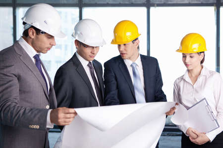 group plan: Business people in hard hats at construction site Stock Photo