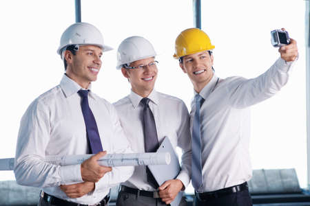 Business people in hard hats are photographed on site photo